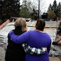 Deux femmes se réconfortent en observant les restes calcinés de leur maison.