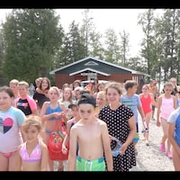 Des jeunes marchent en maillot de bain devant le camp.
