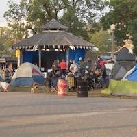 Des tentes autour d'un pavillon dans un petit parc. Des gens se promènent.