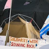 Des tentes, des drapeaux et la banderole « Solidarité avec Standing Rock ».