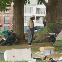 Un homme debout devant sa tente.