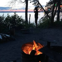 Une personne dans l'ombre regarde le coucher du soleil dans un terrain de camping sur le bord de l'eau. Un feu de camp est allumé.