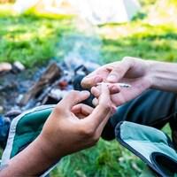 Des gens s'échangent un joint devant un feu de camp.
