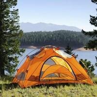 Une tente jaune est installée près d'un lac en montagne.