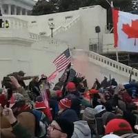 Des personnes tiennent un drapeau canadien lors des émeutes du Capitole de Washington le 6 janvier.