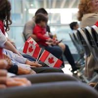 Des personnes munies de petits drapeaux canadiens, assises dans une pièce en attendant la cérémonie de citoyenneté.