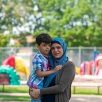Une réfugiée avec son fils dans les bras.