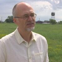 Un homme dans un champ avec des bâtiments industriels au fond.
