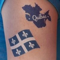 Une dame arbore des tatouages de la carte et du drapeau du Québec.