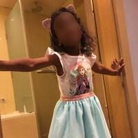 La petite fille, qui porte un déguisement de princesse et des oreilles de chat, prend la pose dans le cadre d'une porte donnant sur une salle de bain. Son visage est flouté.