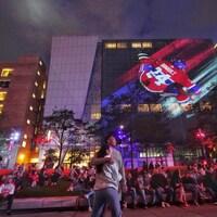 Un couple dans une foule qui regarde un écran au loin. En arrière-plan, une image du joueur Philippe Danault.