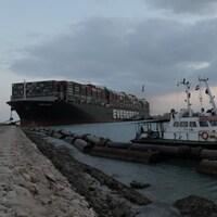 Le navire est entouré de plus petits bateaux.