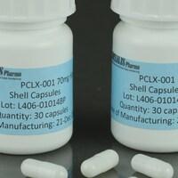 Deux flacons du médicament PCLX-001 avec trois gélules sur une table.