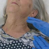 Une main gantée s'approche du visage d'une dame âgée.
