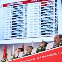 Un homme annonce les résultats du premier tour de la présidentielle tunisienne.