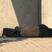 Un homme est couché sous une structure de béton.