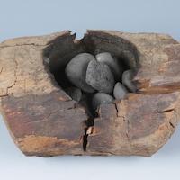 Un contenant de bois avec des pierres à l'intérieur.