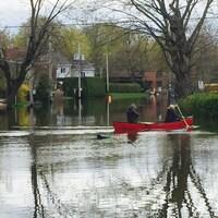 Deux personnes se promènent en canot sur la 13e avenue inondée, à Deux-Montagnes, dans les Laurentides.