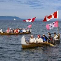 Des gens qui pagaient en habits traditionnels dans des canots d'écorce ornés de drapeaux.