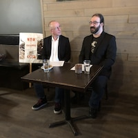 Deux hommes parlent dans un restaurant. Une pancarte indiquant « Non à Gazoduq » est placée près d'eux.