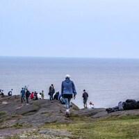 Des touristes visitent un phare au sommet du cap.