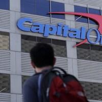 Un homme regarde au loin l'enseigne de Capital One sur un édifice.