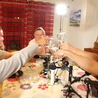Des personnes frappent leurs verres ensemble autour d'une tabe de cuisine.