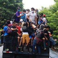 Des dizaines d'hommes et d'enfants ayant grimpé derrière un camion.