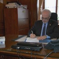 Le ministre des Finances Carlos Leitao signe dans son bureau un arrêté ministériel visant à rembourser deux milliards de dollars sur la dette.