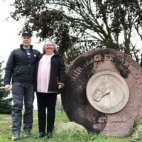Un couple pose pour la caméra près d'un monument.