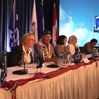 Carolyn Bennett, Clément Chartier et des leaders de la Nation Métisse sont attablés avec des drapeaux métis autour.