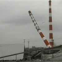 Les deux cheminées rouges et blanches de la carrière Miron, dont une s'effondrant à la diagonale.