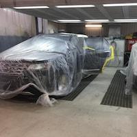 Des voitures enveloppées d'une pellicule de plastique dans le garage d'un carrossier.
