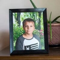 Une photo de Carson Crimeni dans un cadre posé sur un bureau.