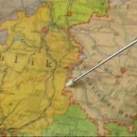 Une baguette pointe sur la ligne rouge d'une carte géographique de l'Allemagne.