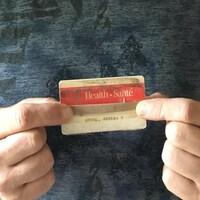 Une carte santé rouge et blanche de l'Ontario endommagée tient avec du papier collant.
