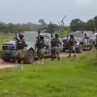 Une dizaine d'hommes armés à côté de camions blindés.
