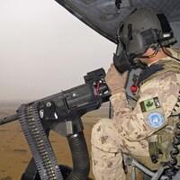 Un soldat canadien est assis dans un hélicoptère, devant un fusil mitrailleur.