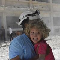 Une fillette pleure dans les bras d'un homme portant un casque blanc.
