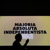 L'ombre d'un homme qui consulte son téléphone portable apparaît devant un écran sur lequel on annonce que les indépendantistes catalans ont remporté la majorité absolue.