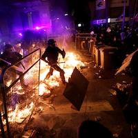 Des policiers masqués et munis de matraques traversent une ligne de cartons enflammés pour affronter les manifestants.
