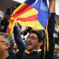 Un homme tient un drapeau catalan au milieu d'une foule réunie dans un local à l'occasion des élections partielles catalanes.