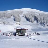 Un chalet au pied d'une montagne enneigée et serpentée par des pentes de ski.