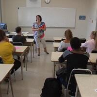 La professeure est debout au milieu de la rangée de bureaux.