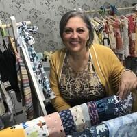 Une femme souriante dans la cinquantaine, portant un chandail par-dessus un haut à motif, est entourée de vêtements qu'elle conrfectionne pour nouveaux-nés jusqu'à l'âge de 6 ans