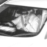 Un homme sur son téléphone cellulaire au volant d'une voiture, filmé par une caméra de surveillance.