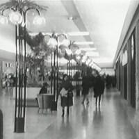 Consommateurs dans un centre commercial qui imite une grande allée.