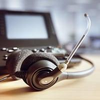Des écouteurs dotés d'un micro posés sur une table, près d'un téléphone.