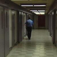 Un agent correctionnel marche dans un corridor de la prison.