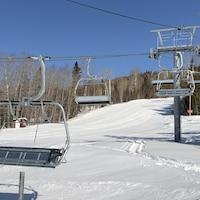 Des traces de motoneige sont visibles dans la neige sous les télésièges immobilisés.